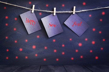 Happy new year on paper with a clothespin, hanging on a rope on a dark wooden background. Greeting card with a happy new year. Holidays.