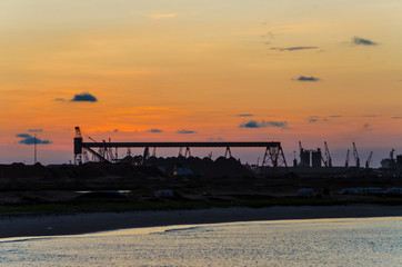 Scenic view over cranes and container port of Pointe-Noire during red sunset