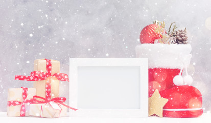Bright christmas mock up with photo frame: festive gift boxes, toys, and fir-cones in red santa's boot under snow. New year concept. Text space. Greeting card template