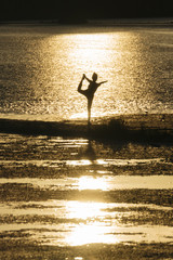 Young Japanese woman practicing yoga exercises near a river in a summer day in the city at sunset