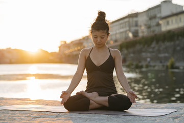 Woman practicing yoga near a river in the city