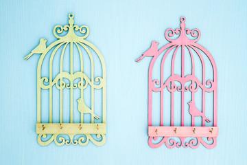 Deurstickers Vogels in kooien Wooden Key Hangers with Bird Cage Shape on Blue Wooden Background