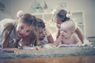 Sisters playing with baby brother. On the move.