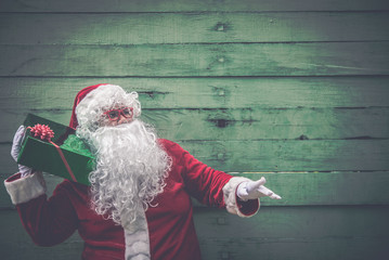 Portrait of santa claus holding gift box on wood background