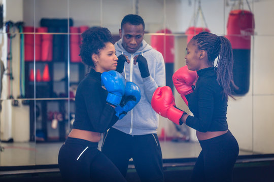 Experienced boxing trainer supervising and teaching two female boxers indoors