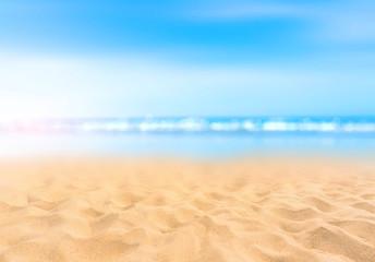 Sandy beach with blurry blue ocean