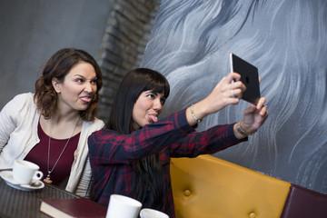 Ragazze in un bar si fanno un selfie con un tablet divertite facendo le smorfie