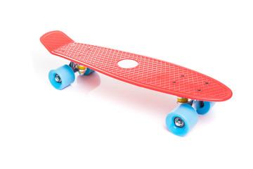 Red plastic skateboard on white background