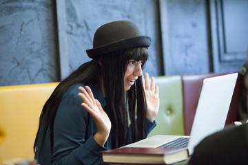 Giovane studentessa con cappello a bombetta guarda il computer incredula con le mani alte seduta in un divano colorato.