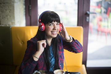 Ragazza con cuffie ascolta la musica dal suo cellulare seduta davanti a un bancone in legno