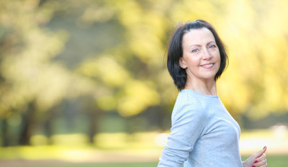 Portrait of mature woman weared in sports clothes in the park