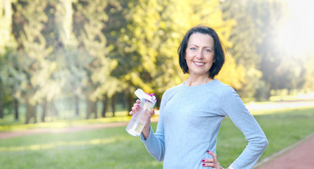 Sporty mature woman hold bottle with water outdoor on sunny day in the park