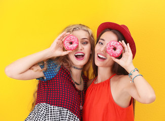 Attractive hipster girls posing with donuts on color background
