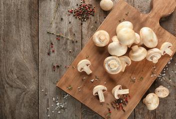 Fresh champignon mushrooms on wooden board