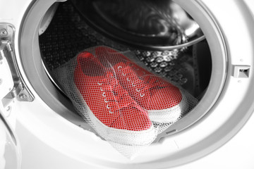 Mesh with red sneakers in washing machine, closeup