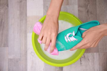 Woman washing sneaker with rag over plastic basin, closeup
