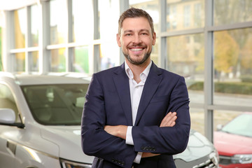 Handsome car salesman in dealership centre
