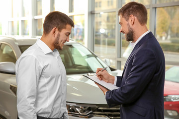 Handsome car salesman with trainee in dealership centre