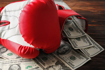 Boxing gloves and money on wooden background