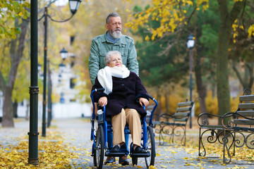 Senior man with his wife in wheelchair outdoors on autumn day