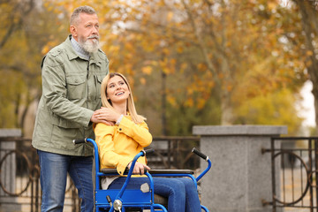 Senior man with his daughter in wheelchair outdoors on autumn day