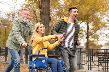 Happy woman in wheelchair with her family outdoors on autumn day