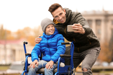 Man with his son in wheelchair taking selfie outdoors on autumn day