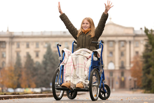 Happy teenage girl in wheelchair outdoors on autumn day