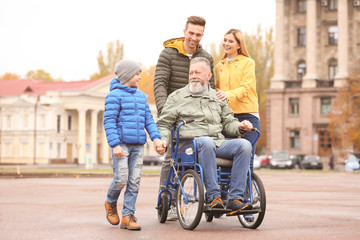 Elderly man in wheelchair with his family outdoors on autumn day