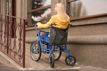 Woman in wheelchair on ramp outdoors