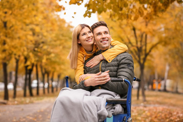 Woman with her husband in wheelchair outdoors on autumn day