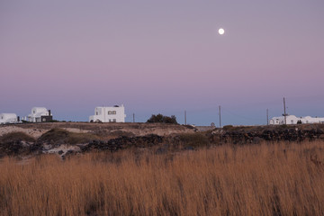 grassland with white houses on horizon after sundown at full moon