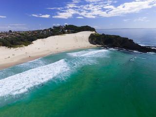 Luftbild mit Blick auf steilen Sandstrand und in das Wasser ragenden Felsvorsprung