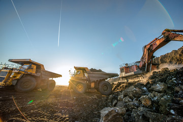 Big yellow dump truck and excavator in the coal mine, fisheye