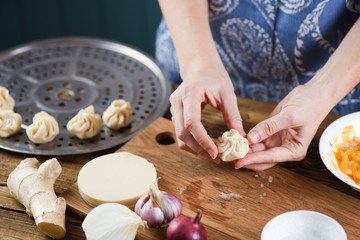 Woman cooking traditional Nepalese purse shaped dumplings momos on rustic wooden table