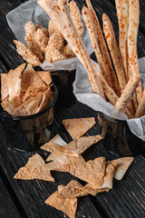 Snacks for beer on dark wood background. Grissini, chicken grilled breast, pita chips