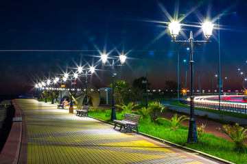 Night quay paved with sidewalk tiles, along the path are benches and lampposts. Embankment on the Black Sea coast, Sochi, Russia.