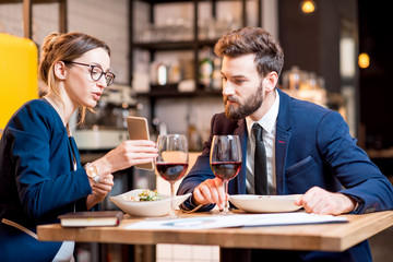 Caucasian business couple dressed strictly in the suits working together with smart phone sitting at the restaurant during the dinner