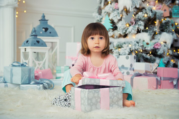 Positive cheerful baby girl sitting with Christmas gift near Christmas tree. Happy New Year
