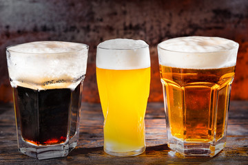 Three glasses with freshly poured light, unfiltered and dark beer on dark wooden desk