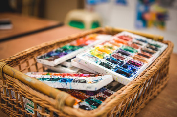 Old watercolor paints in basket