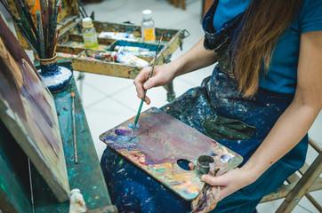Artist paints on canvas in studio