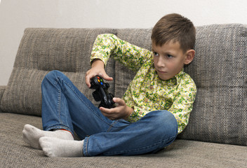 Boy with joystick playing video game at home