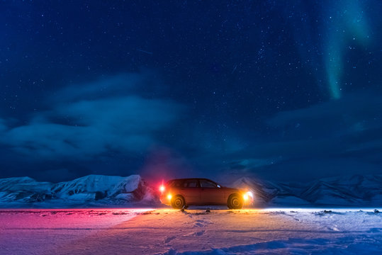 The polar arctic Northern lights aurora borealis sky star in Norway Svalbard in Longyearbyen city car the moon mountains