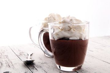 Hot chocolate or coffee with whipped cream in glass.