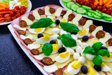 Buffet catering food with basil, egg, mozarella, sausage, ham, olive, carrot, tomatoes and others vegatables arangement on table