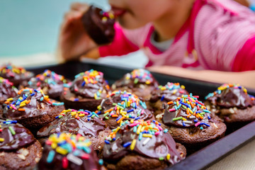 Portrait of sweet little child eating cake, decorated muffins