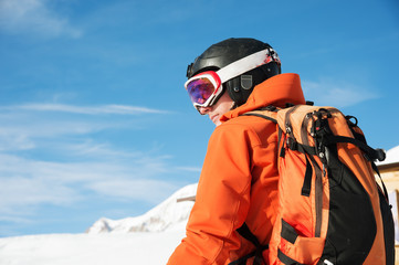 Portrait of a skier in an orange overall with a backpack on his back in a helmet stands against the background of a beautiful Caucasian mountain landscape