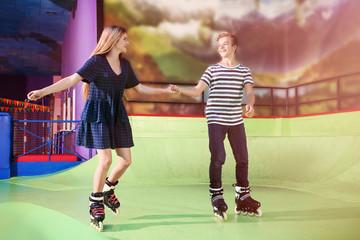 Cute teenage couple at roller skating rink