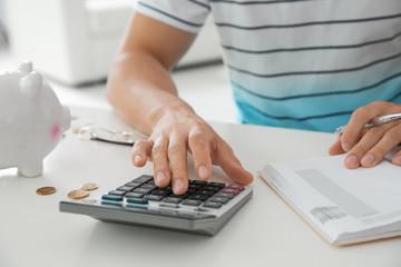 Young man counting taxes at table, closeup